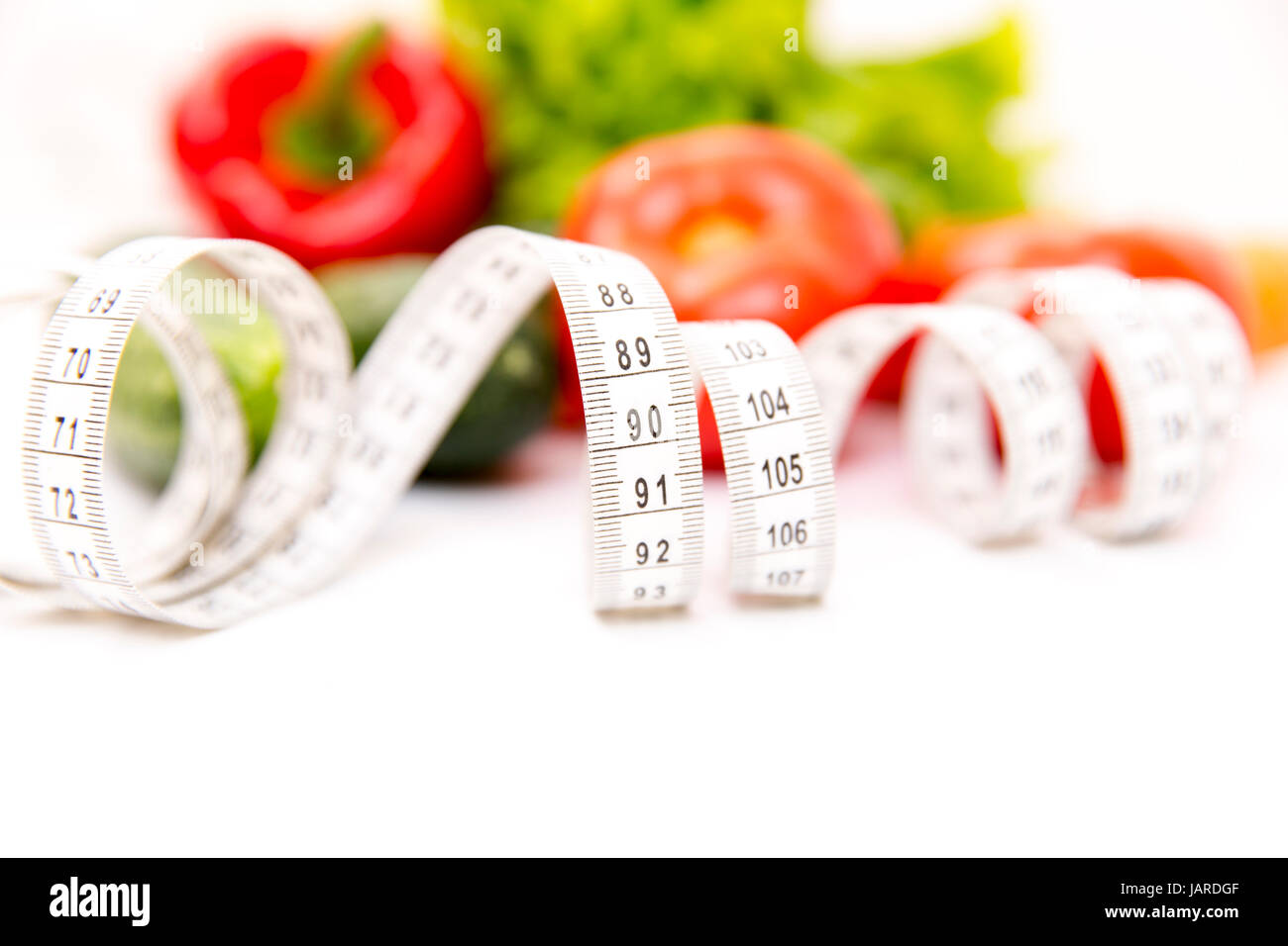 Fitness and healthy food diet concept. Fresh green vegetables, measuring tape isolated on white background. Closeup - Stock Image