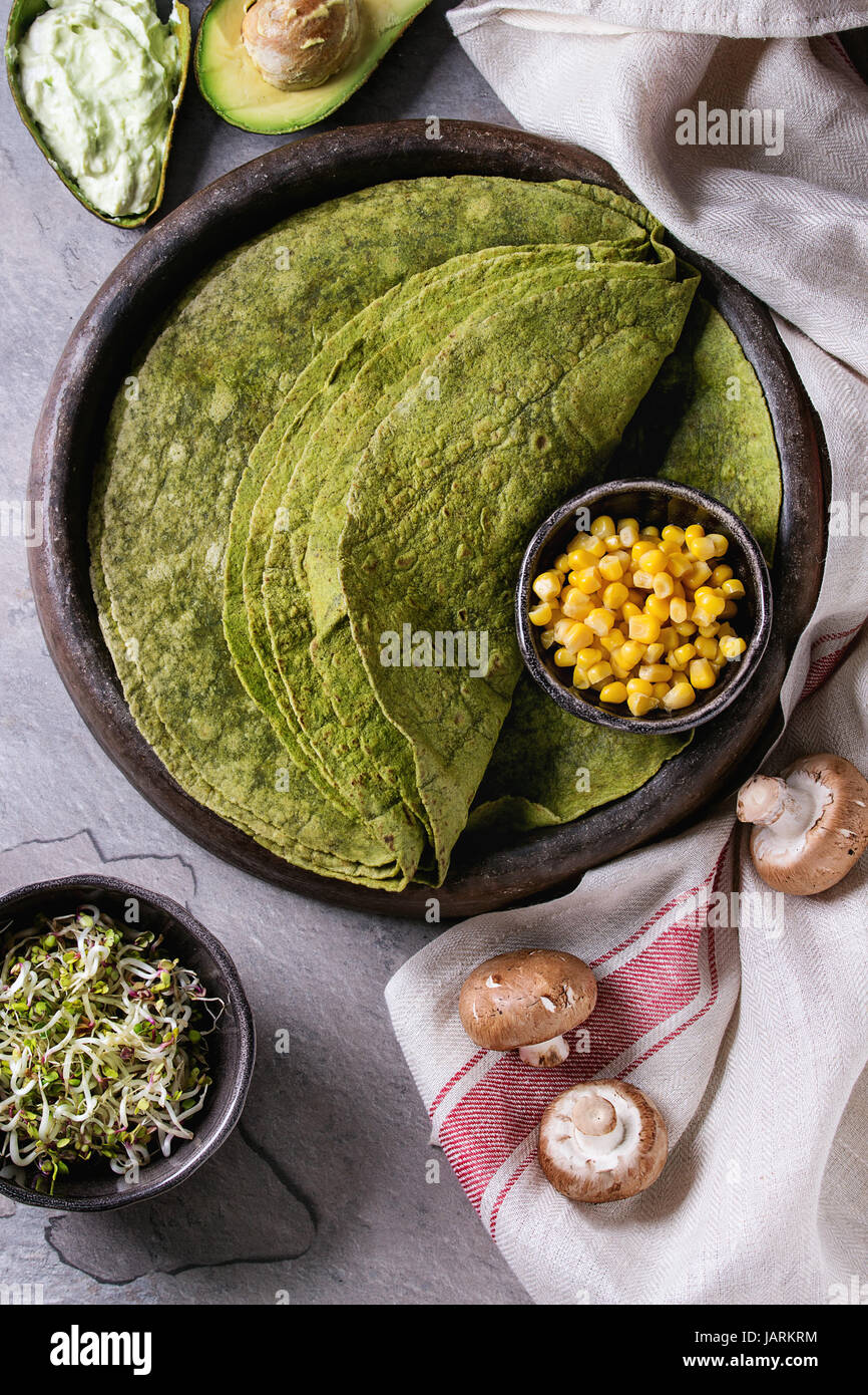 Green spinach matcha tortilla with vegan ingredients for filling. Sweet corn, avocado, green paprika, sprouts, mushrooms - Stock Image