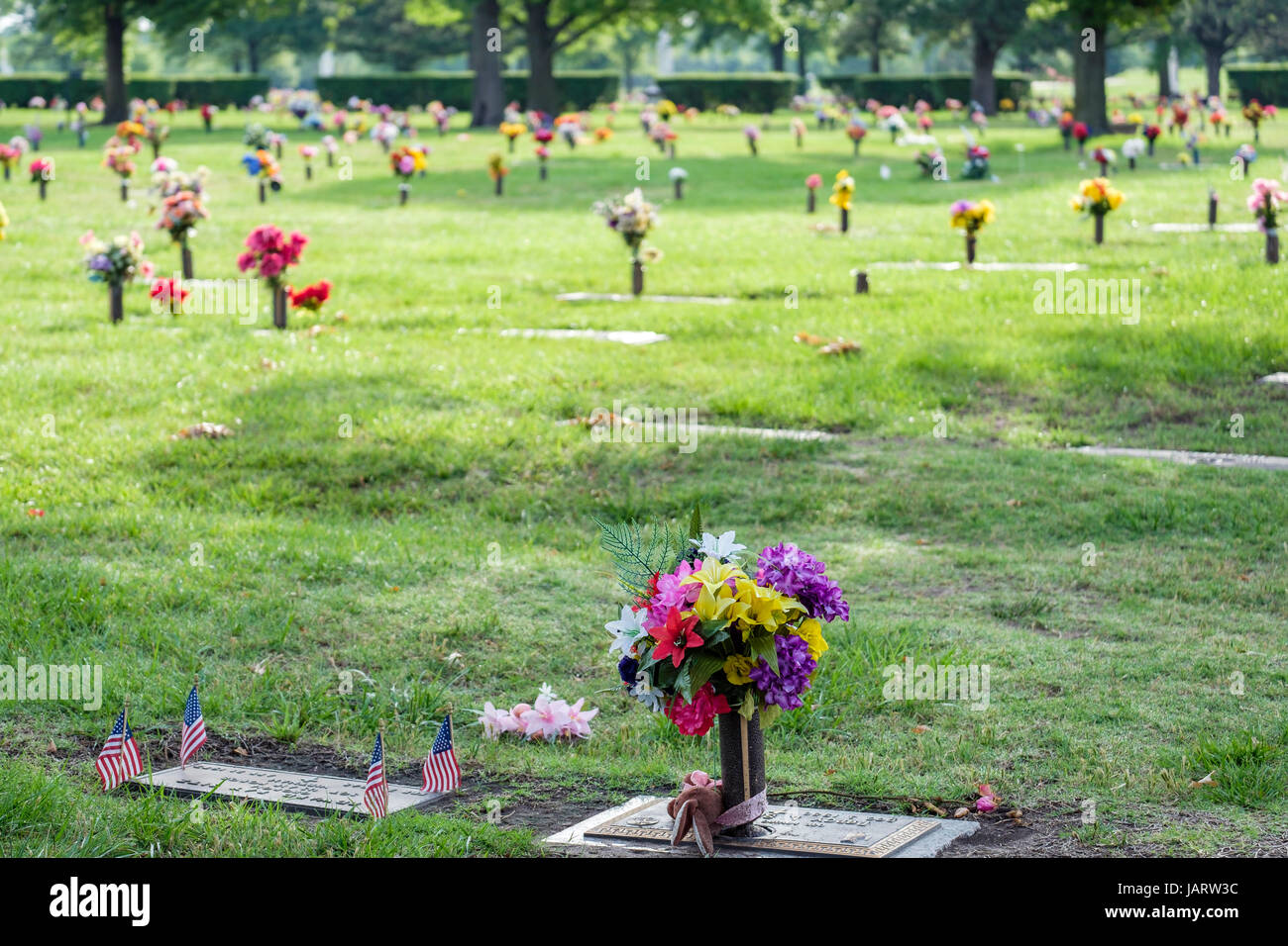 Gravesite floral decorations honoring the dead on Memorial Day in a cemetary in Wichita, Kansas, USA. - Stock Image
