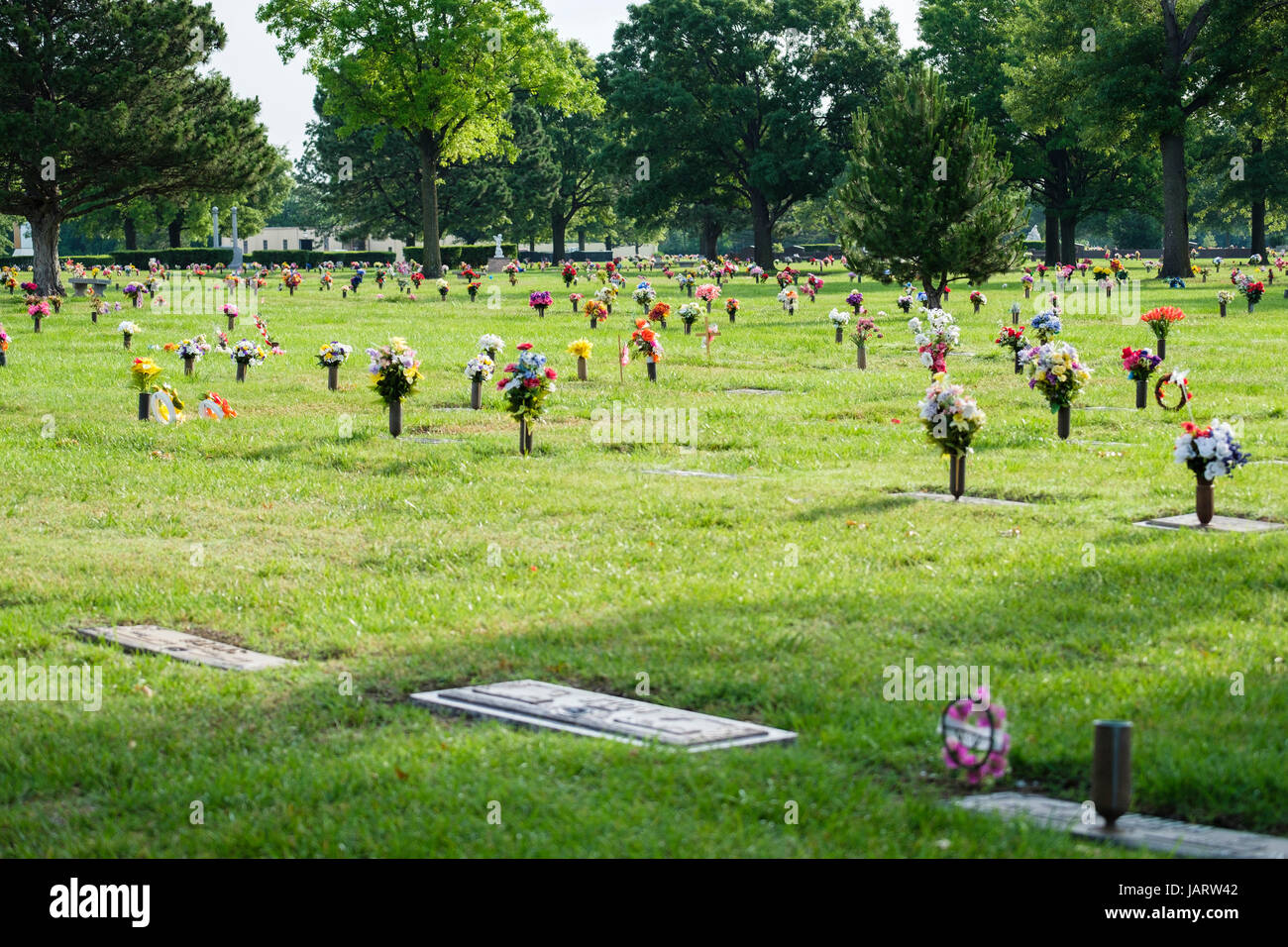 Gravesite floral decorations honoring the dead on Memorial Day in a cemetary in Wichita, Kansas, USA. Stock Photo