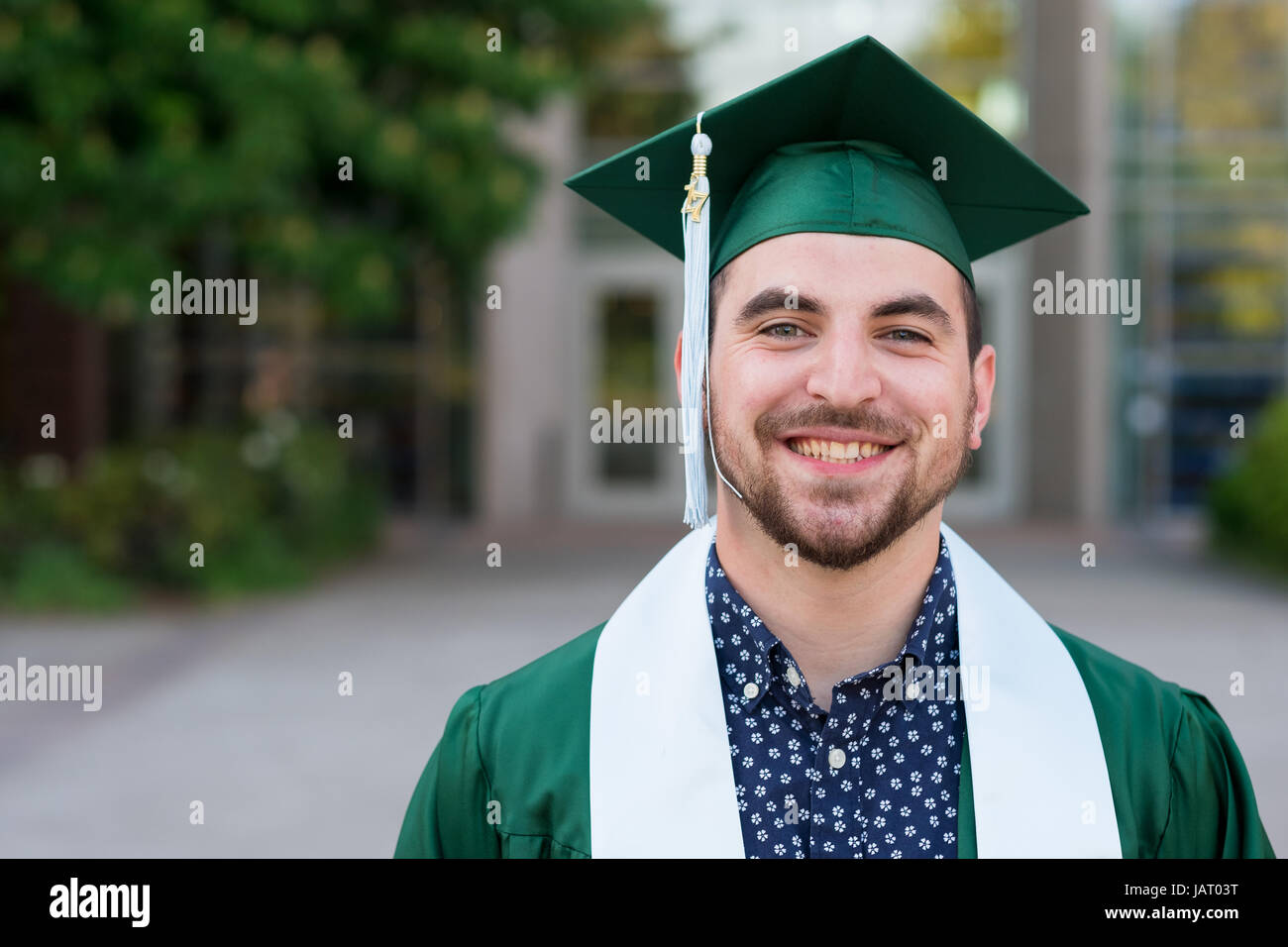 College senior poses for a graduation photo on campus in his cap and ...