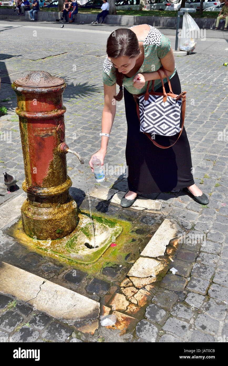 Woman filling water bottle at public drinking fountain (fontanelle spigot) in Rome - Stock Image