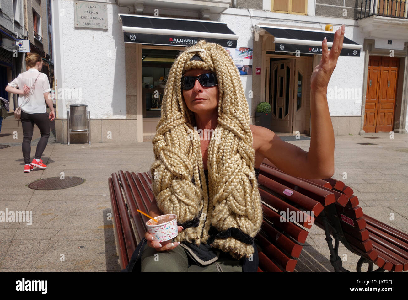 German woman with stunning natural hair braided with wool taking a rest while walking the Camino de Santiago pilgrims - Stock Image