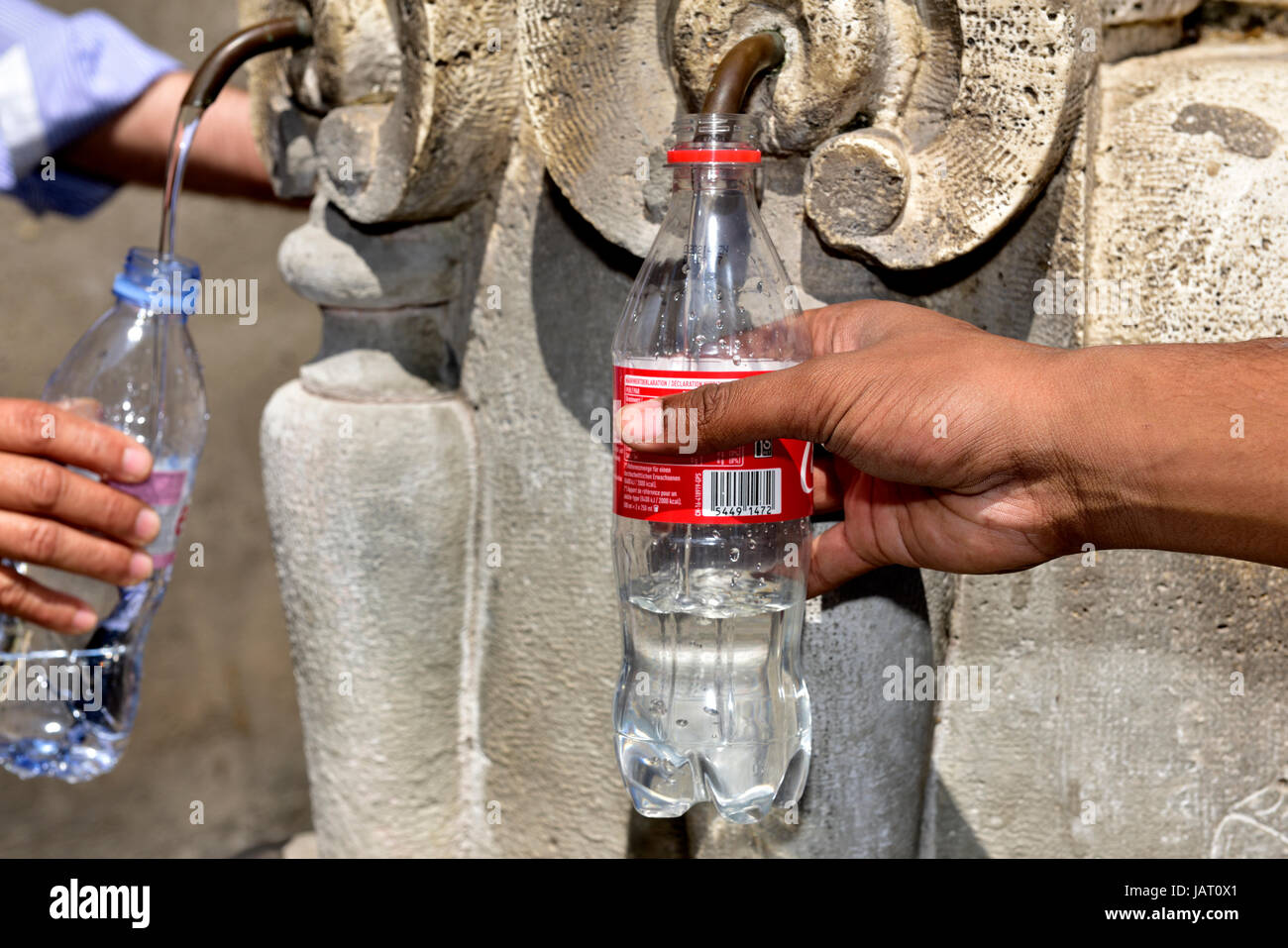 People filling water bottle at public drinking fountain (fontanelle spigot) in Rome - Stock Image
