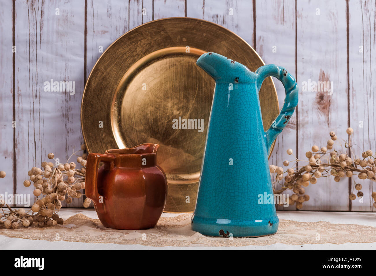 Vintage background with vases and a plate and plant with wood background - Stock Image