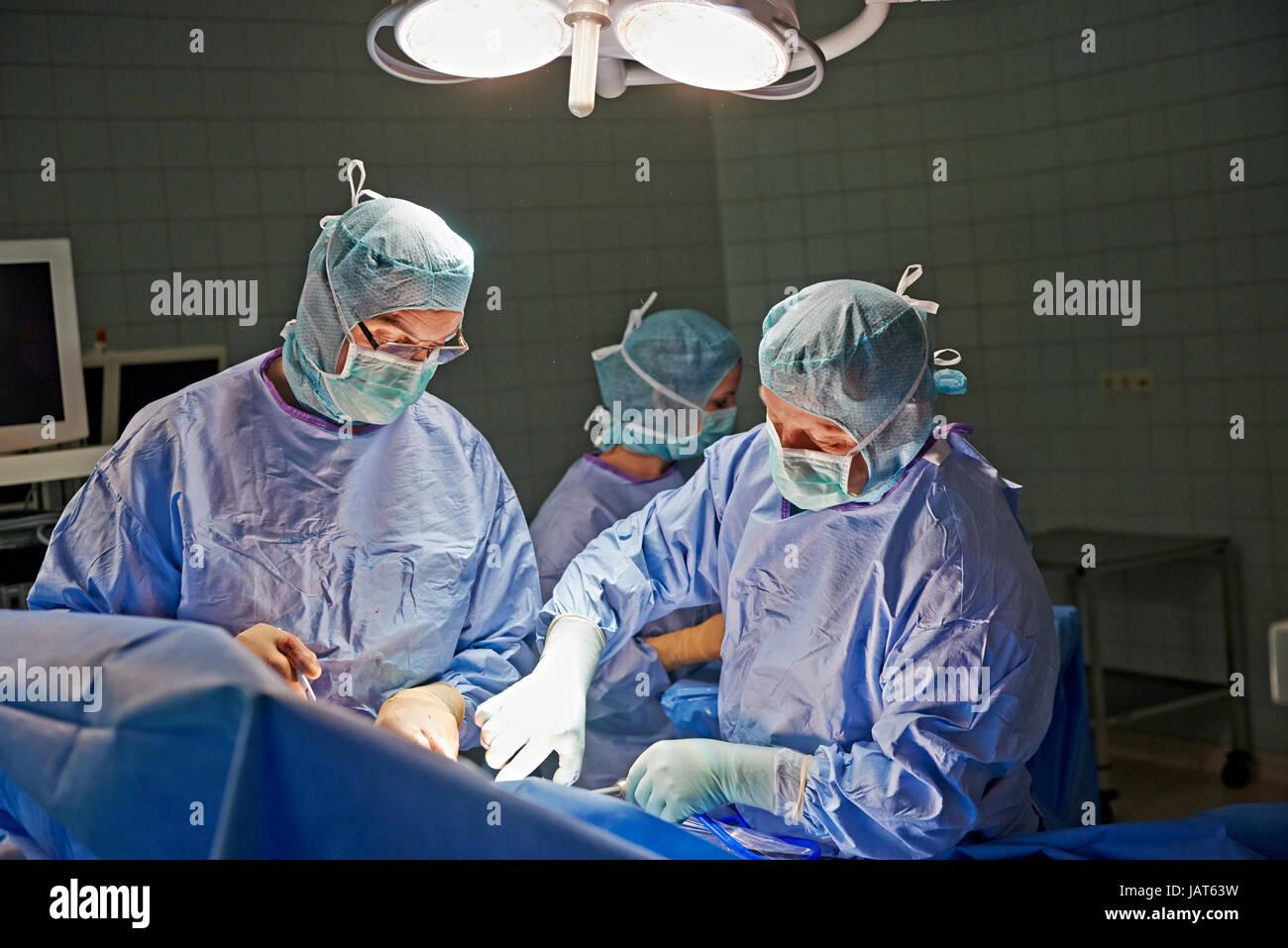 team of surgeons and nurses performing laparoscopic minimally invasive surgery - Stock Image
