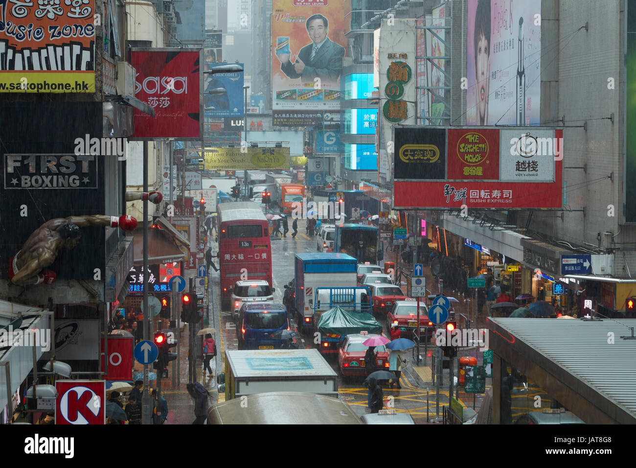 Rain, signs and traffic congestion on Sai Yeung Choi Street, Mong Kok, Kowloon, Hong Kong, China - Stock Image