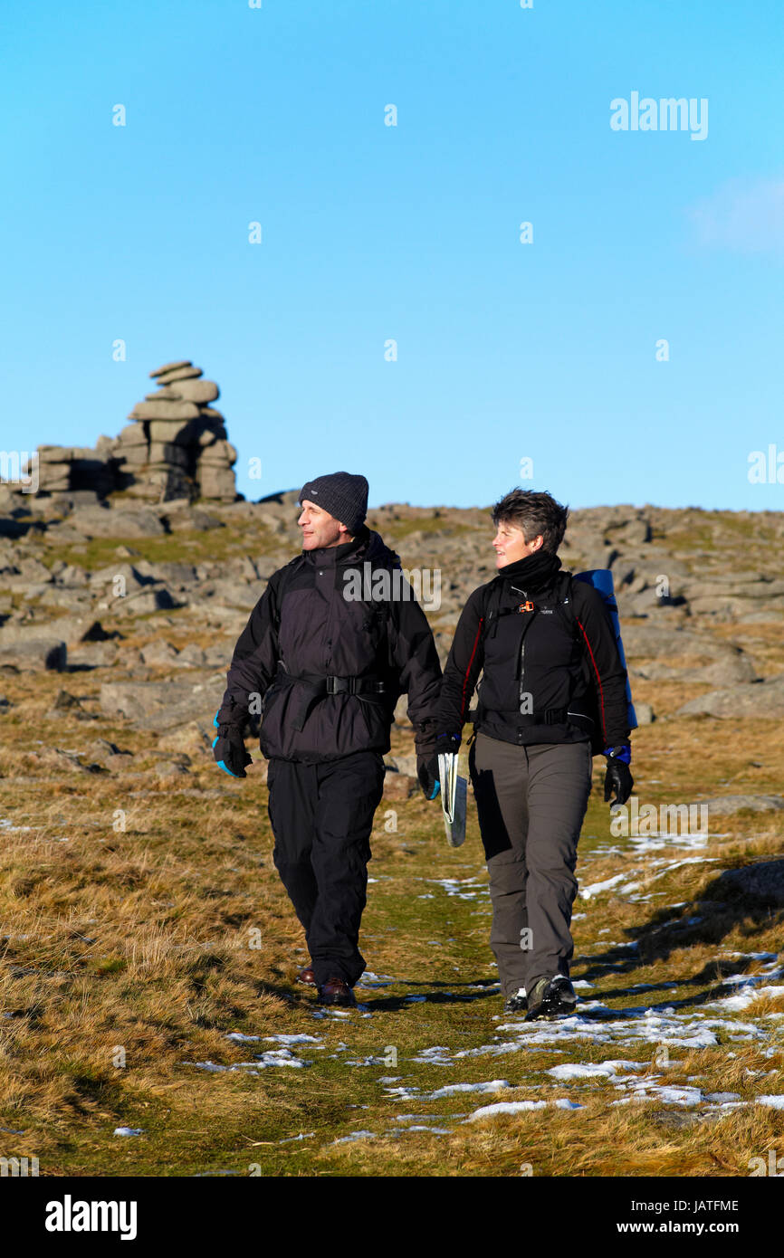 Hikers walking across open moorland on Dartmoor - Stock Image