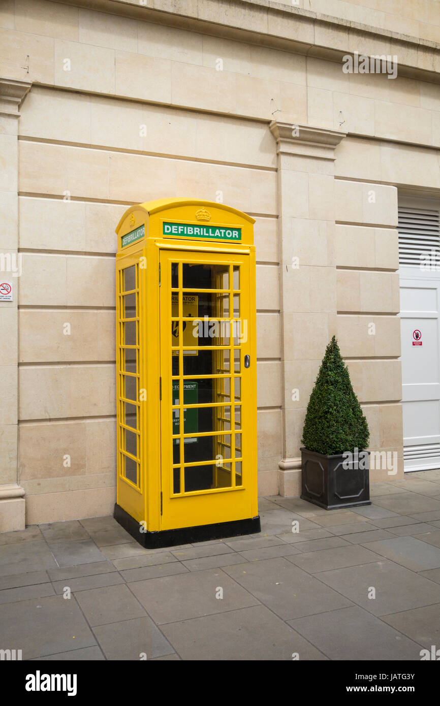 An Automatic Electric Defibrillator, plus first aid equipment and phone installed in a yellow telephone box, Southgate - Stock Image