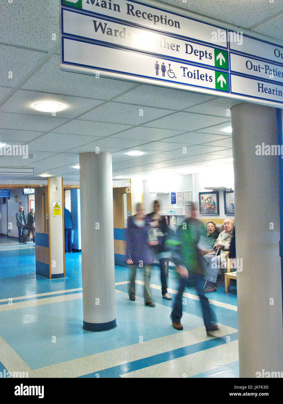 Entrance to a UK NHS hospital with patient and staff walking through, blurred through movement. - Stock Image
