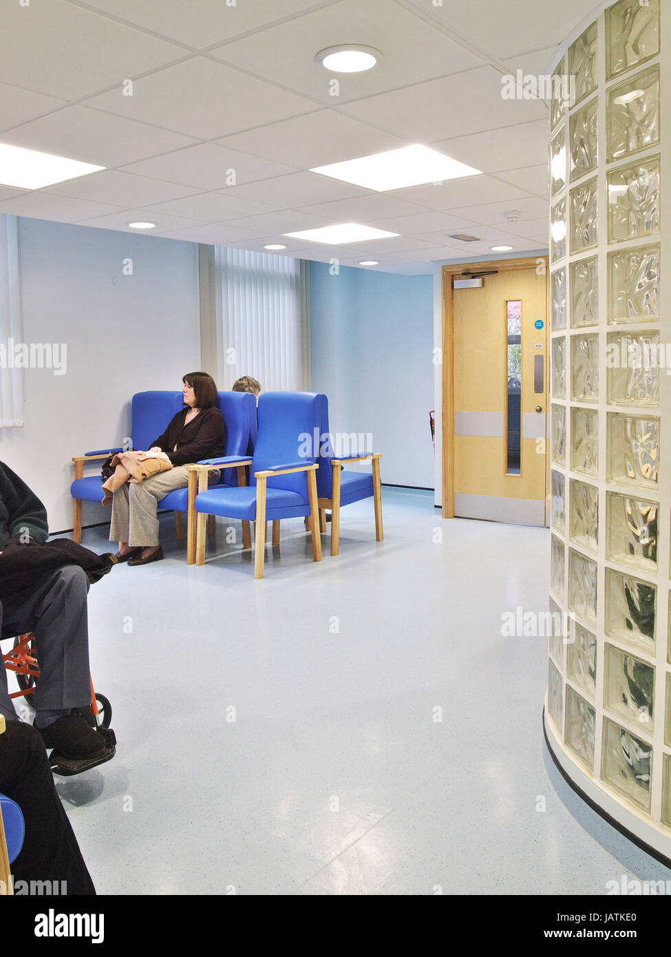 Waiting room in a large UK general hospital, showing patients and staff waiting for appointment - Stock Image