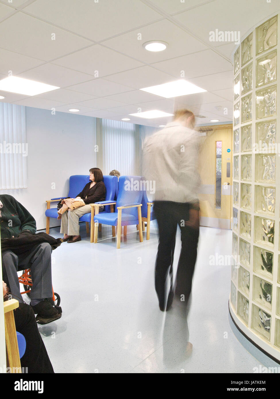 Patients sitting in NHS hospital waiting area, as a doctor walks through the frame, blurred through movement - Stock Image