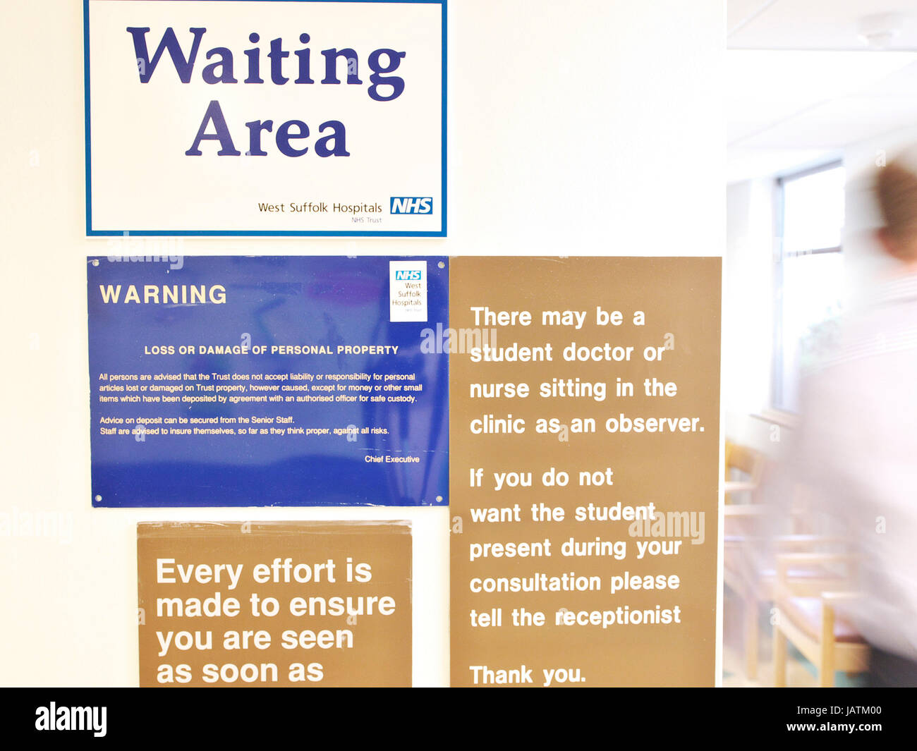 Waiting area signage in a NHS uk hospital as a doctor walks through the frame, blurred by his movement. - Stock Image
