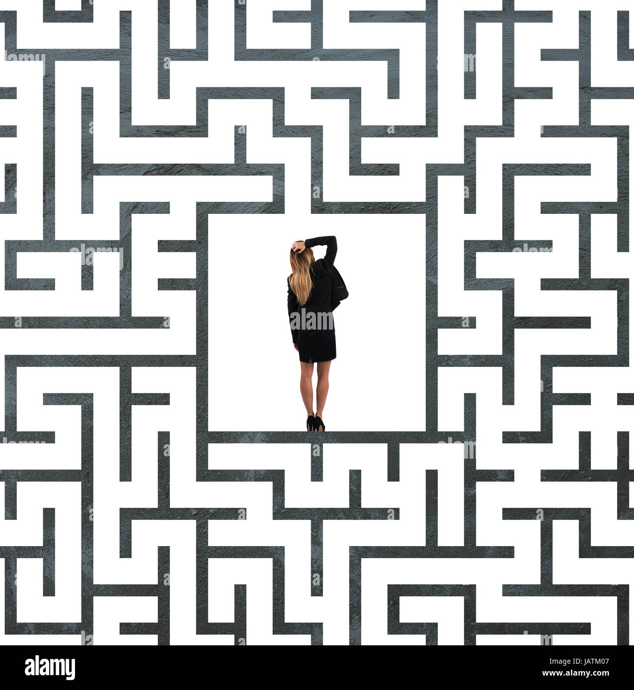 Confused businesswoman at the center of a maze - Stock Image