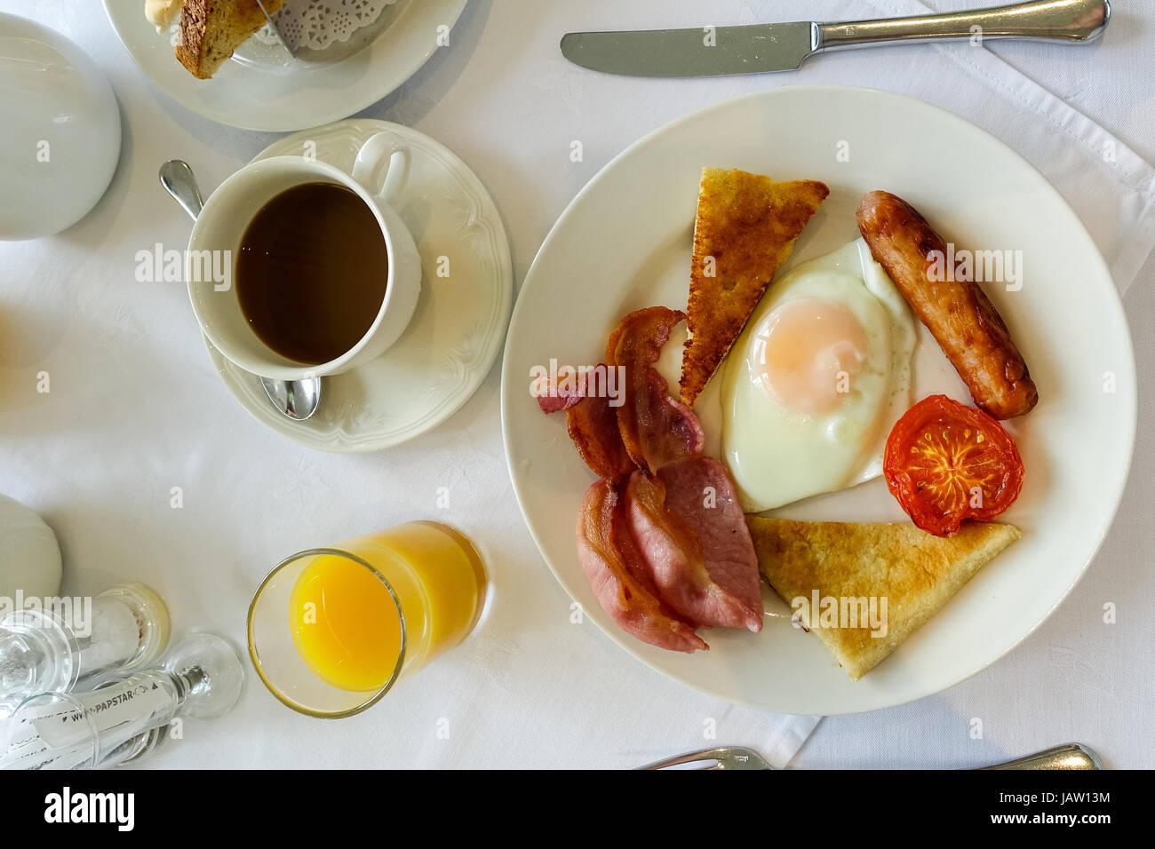 Ulster fry, full breakfast including fried egg, bacon rashers, tomato, sausage, soda bread and potato bread. Orange - Stock Image