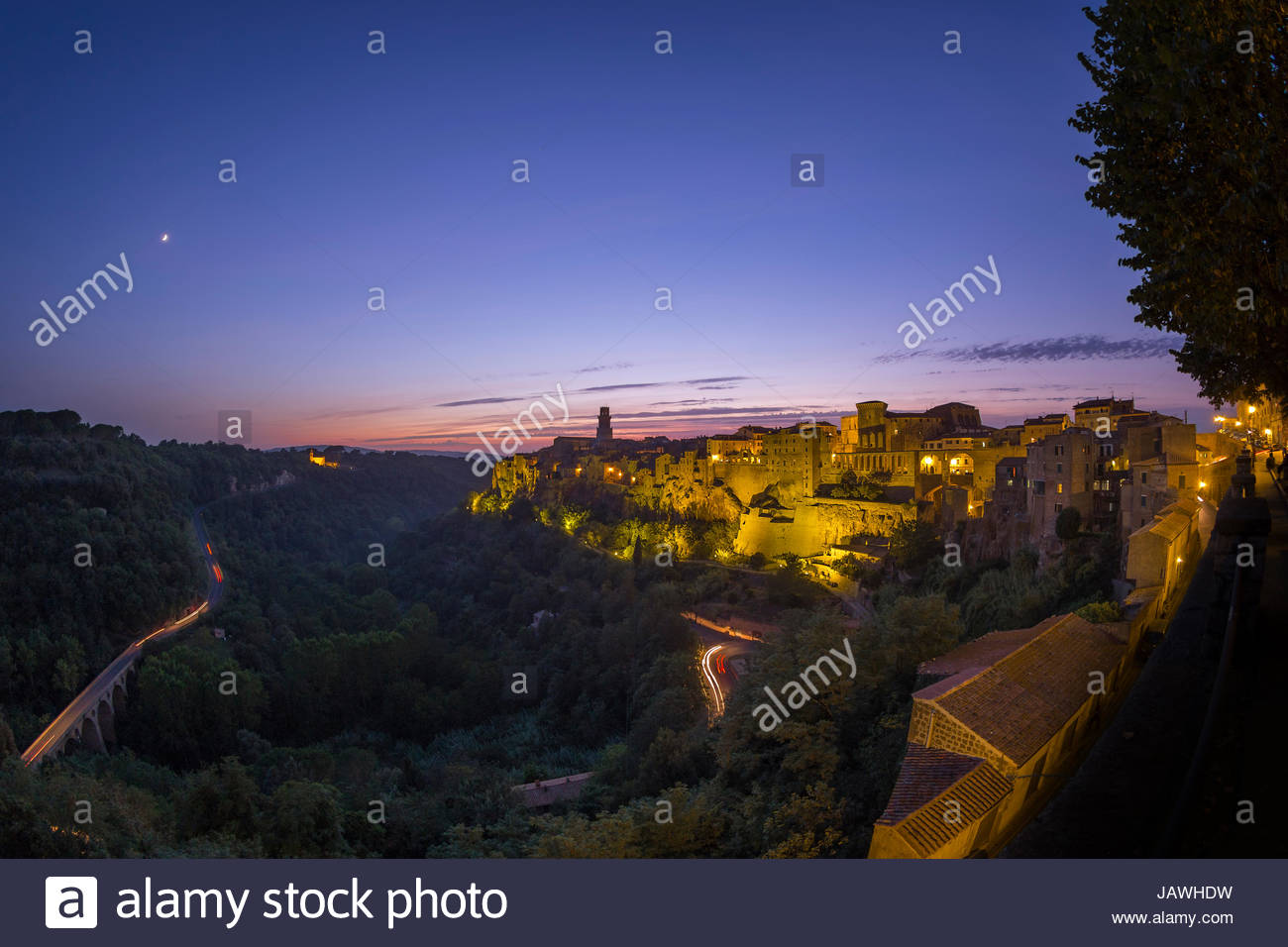 The moon at dusk over Pitigliano, a Medieval town built on top of a tuff cliff, in Tuscany. - Stock Image