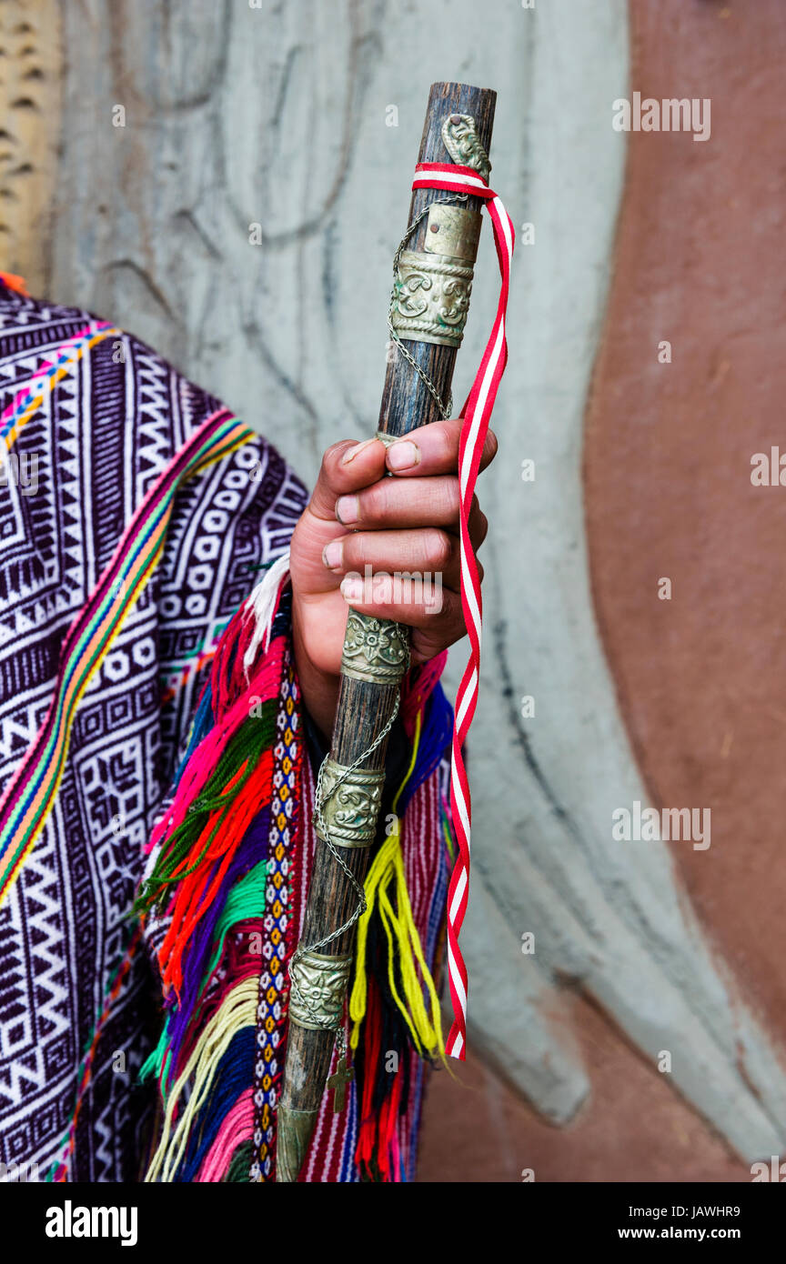 An Amaru man wearing a colourful handwoven poncho holding a brass and timber flute. - Stock Image
