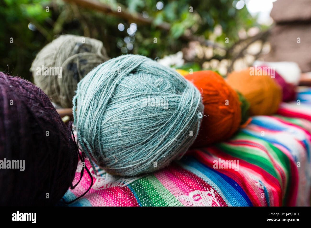 Amaru people using natural dyes to colour sheeps wool to make balls of yarn. - Stock Image