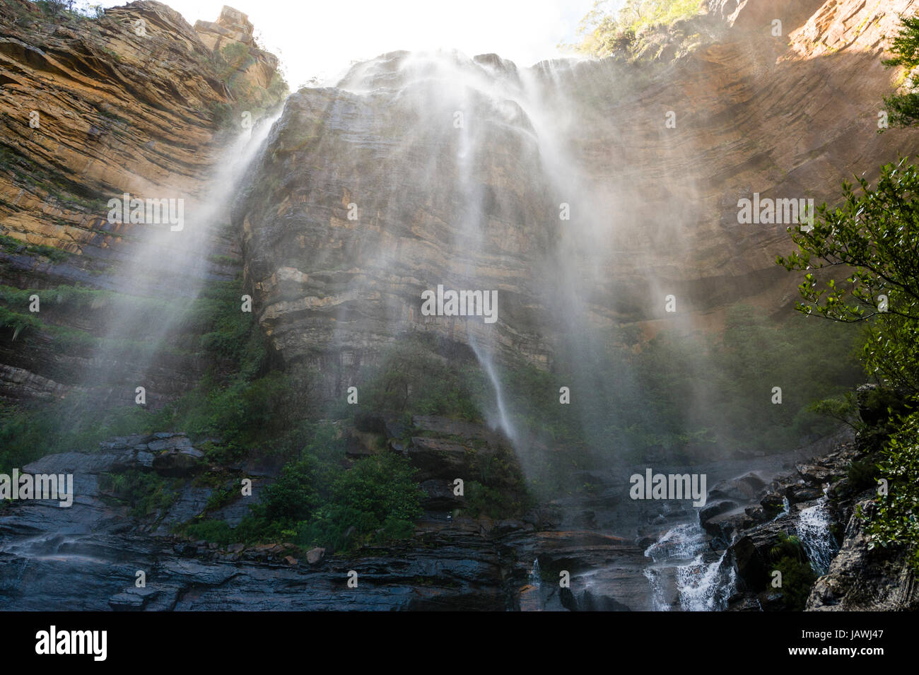 A curtain of mist and water cascades from a waterfall on a sandstone cliff. - Stock Image