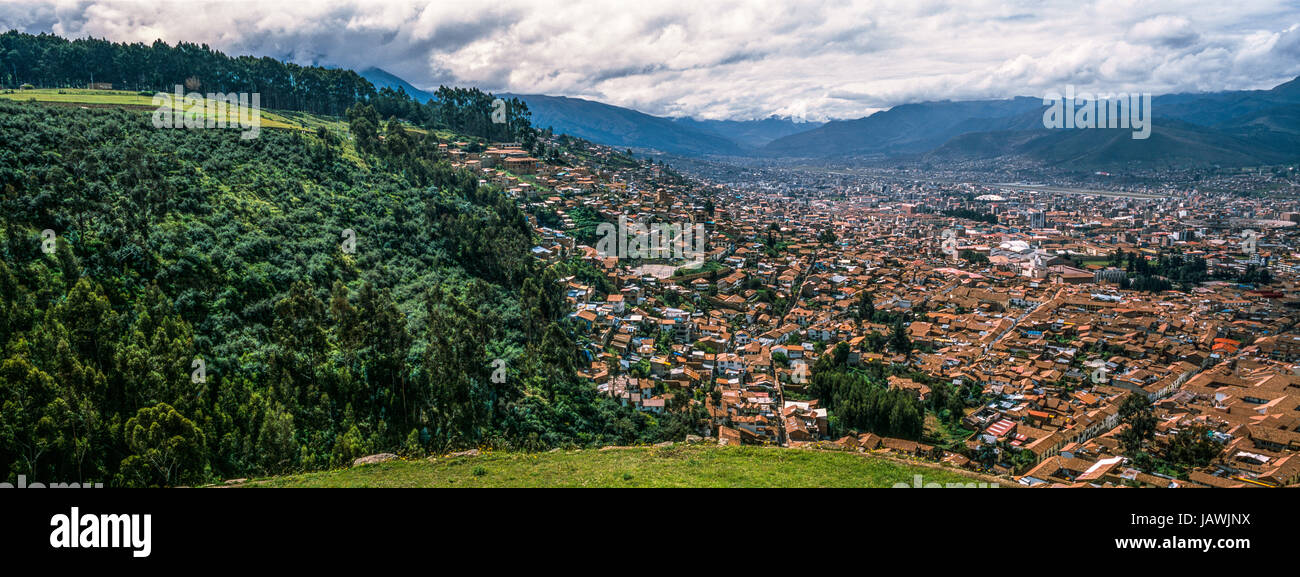 The city and suburbs of Cusco fill an Andes valley with terracotta roof tiles. - Stock Image
