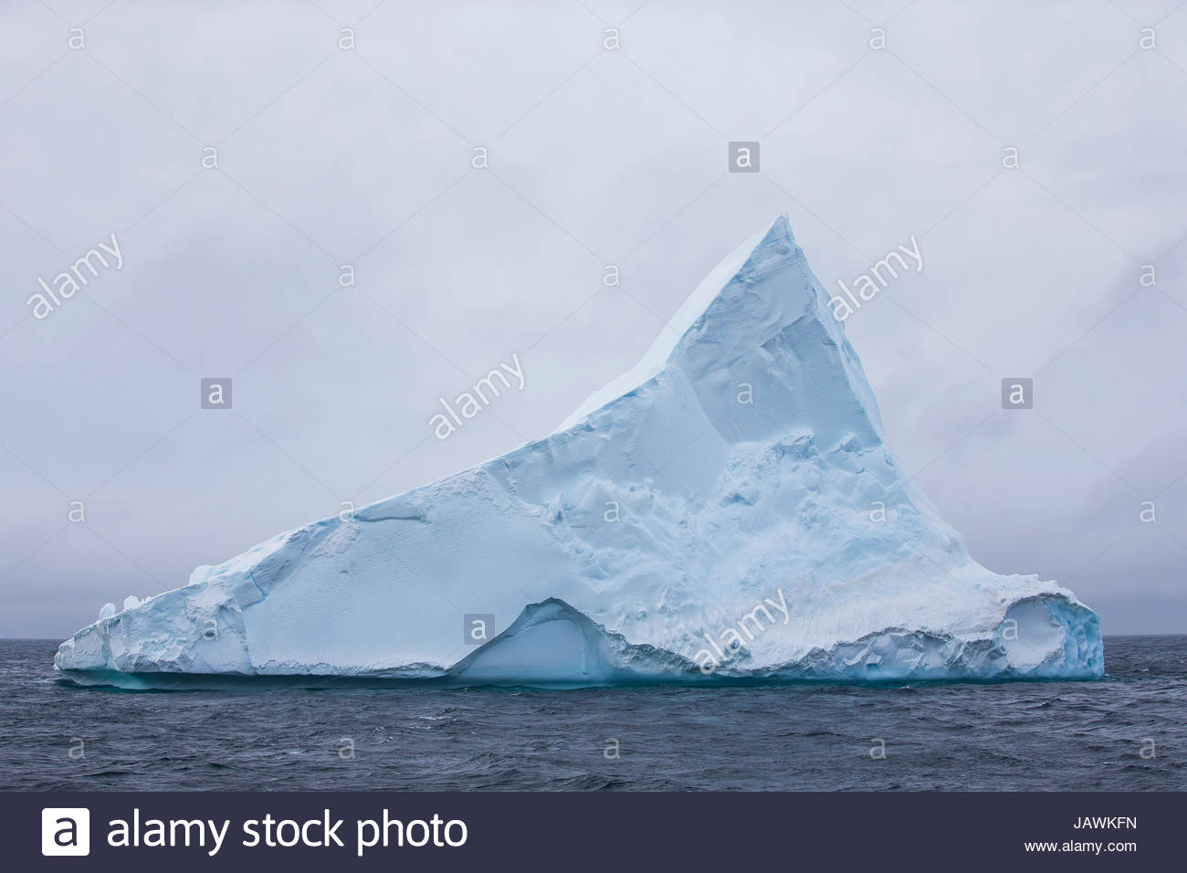 Tabular iceberg with a point in Antarctica. - Stock Image