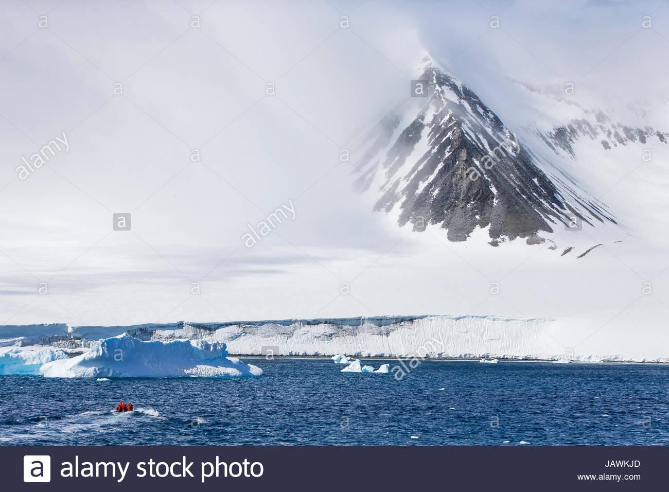 A small Zodiac heading to the coast of Antarctica. - Stock Image