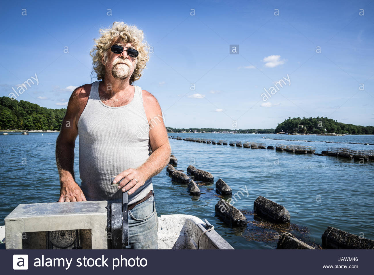 An oyster fisherman drives a boat down the river along his oyster beds. Stock Photo