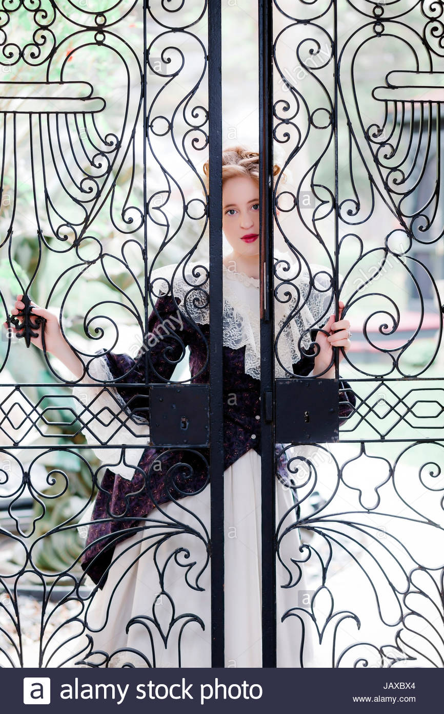 wrought iron fence victorian. Victorian Woman Peering Through A Wrought Iron Fence Gate