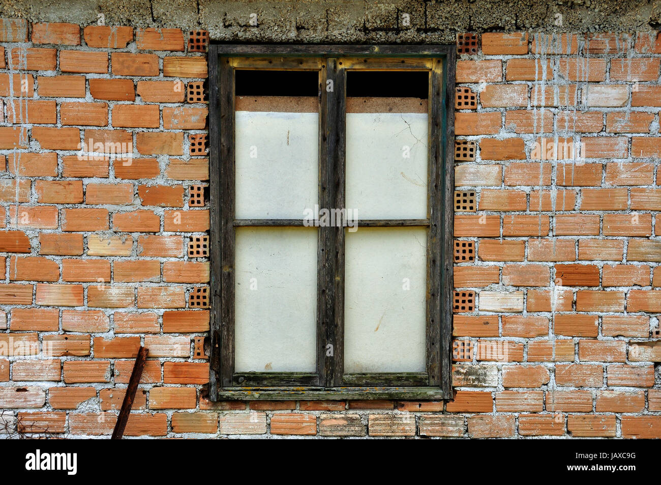 Stained brick wall and boarded up window. Abandoned house detail. Stock Photo