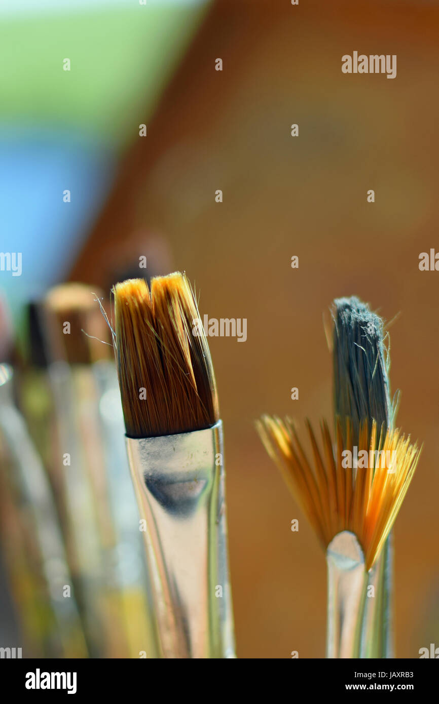 Close up of paint brushes outdoors. Selective focus vertical image - Stock Image