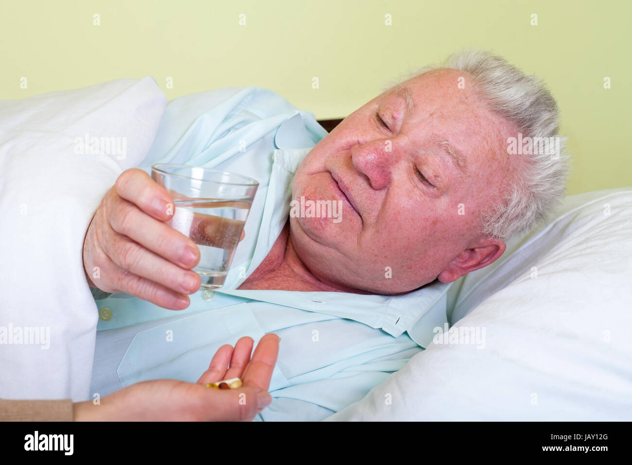 Picture of a sick old man in bed, his caregiver giving him medicine - Stock Image