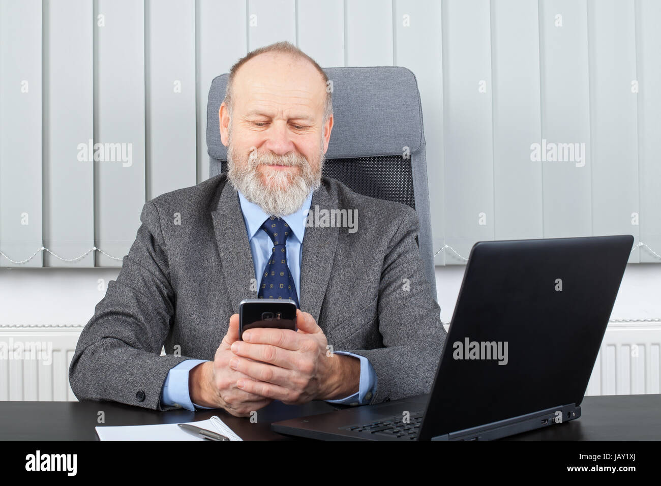 Picture of a happy businessman reading a text message - Stock Image