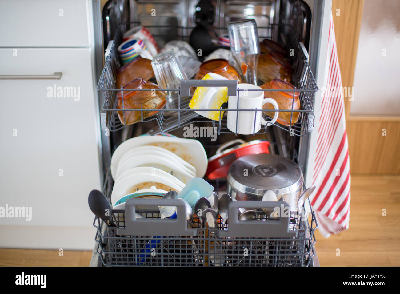 Dishwasher, filled with dirty dishes and glasses in a ...