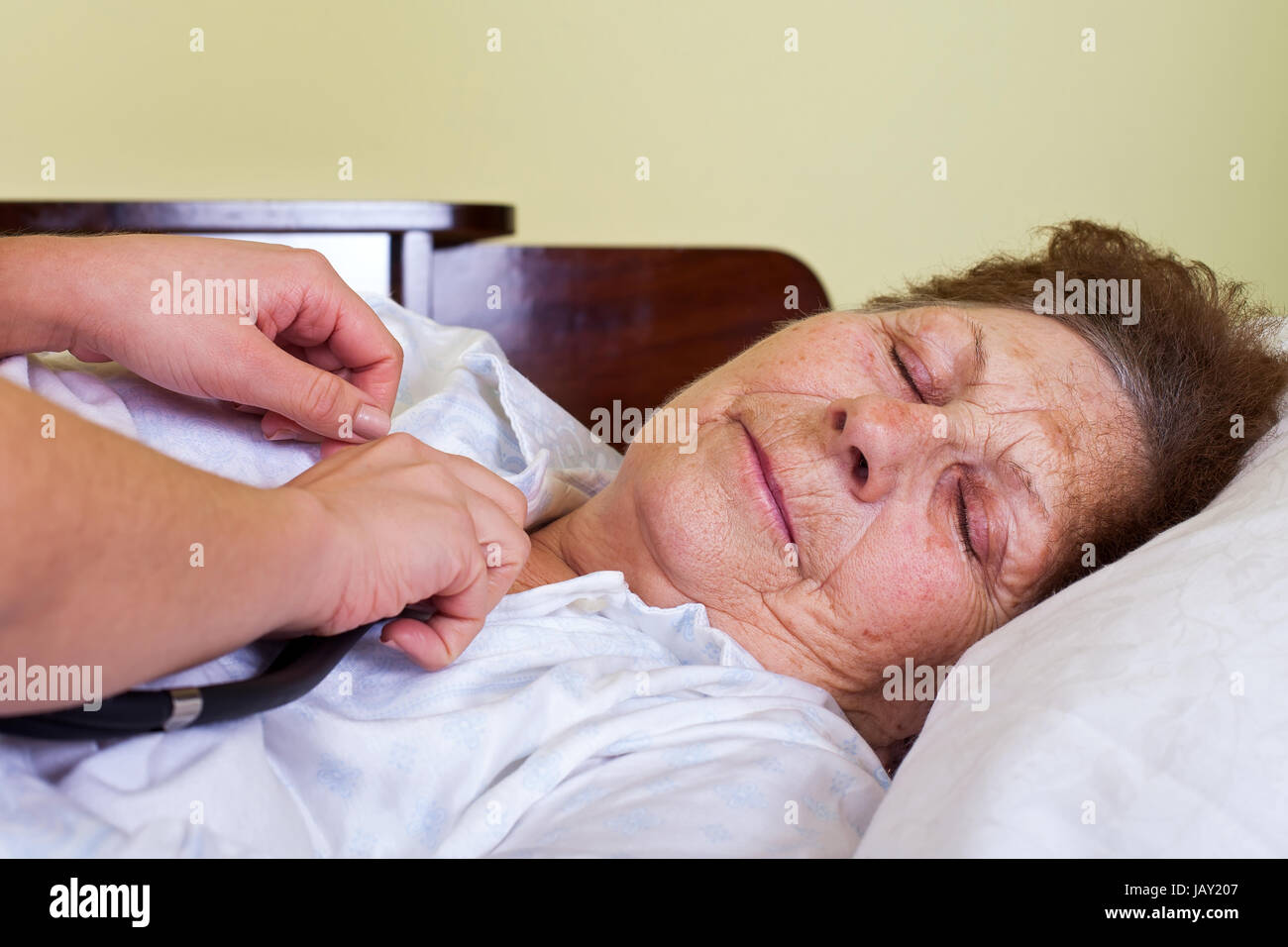 Picture of a bed ridden elderly woman with her carer - Stock Image