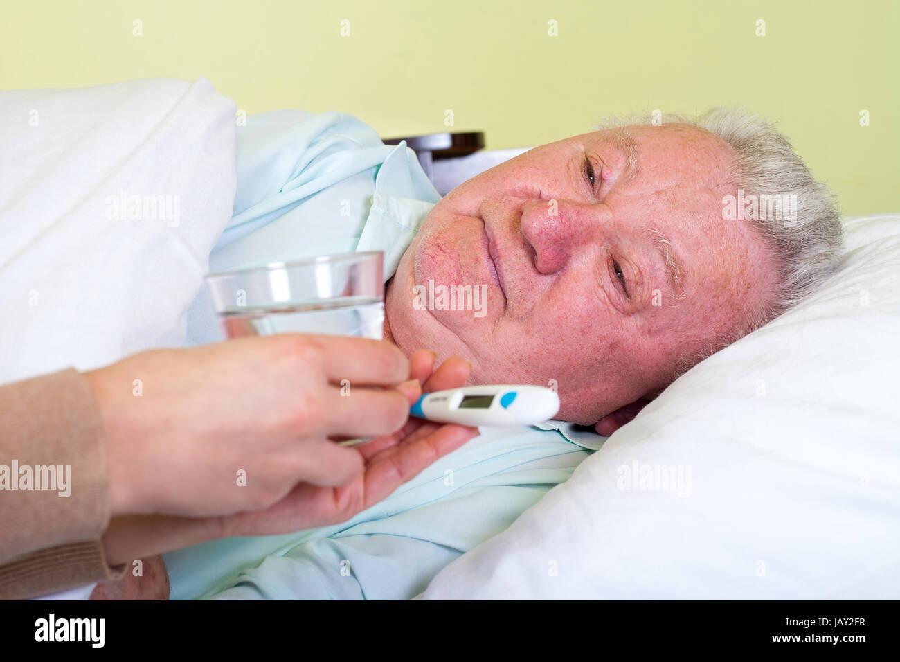 Picture of a bedridden elderly man having high temperature - Stock Image