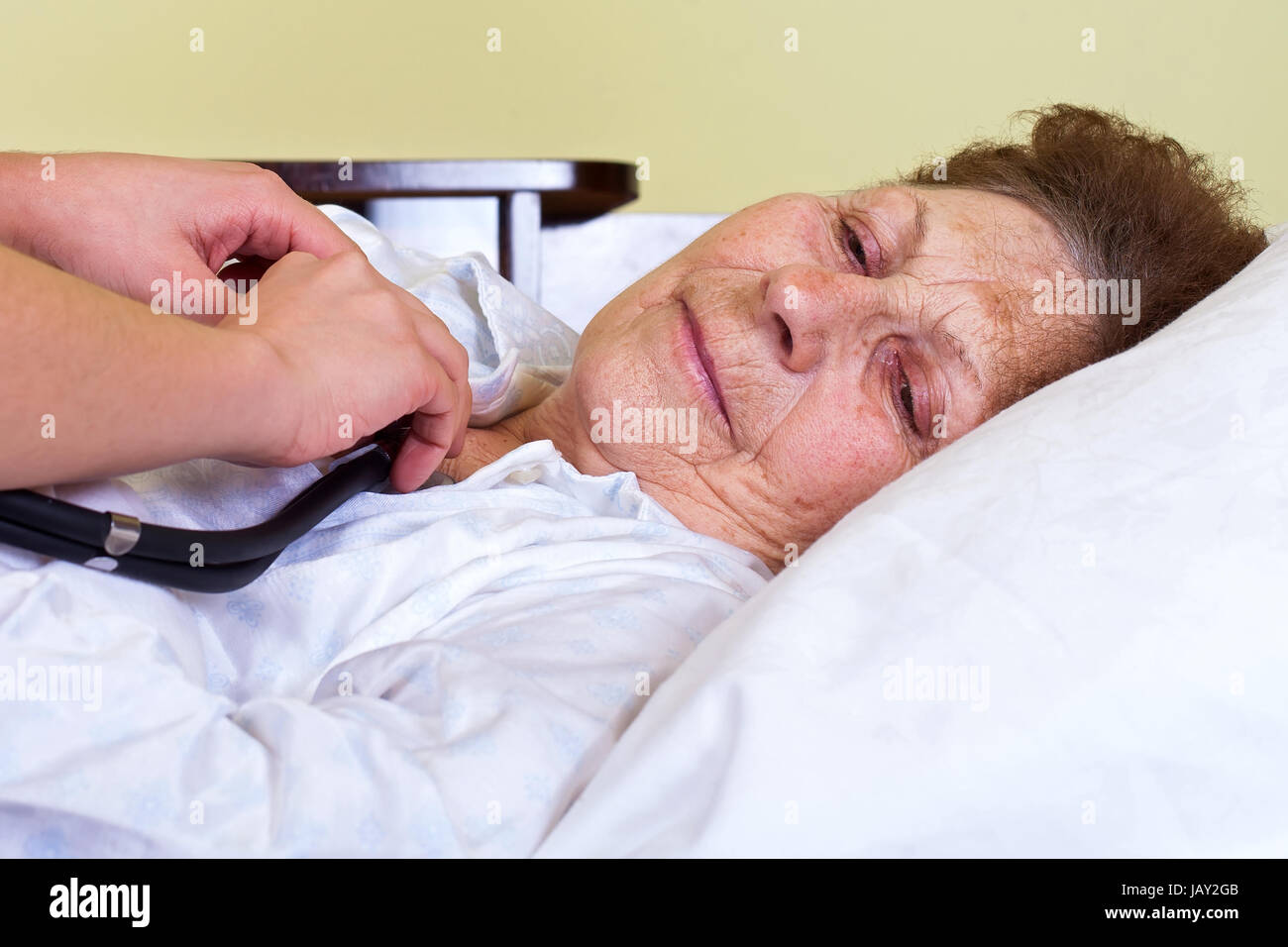 Picture of a bed ridden woman with her carer - Stock Image