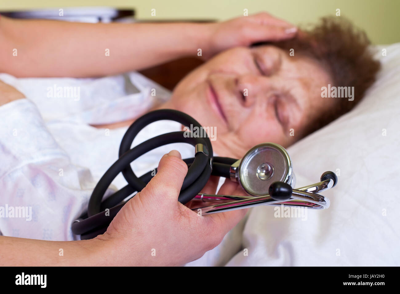 Picture of a sick elderly woman with her carer holding a stethoscope - Stock Image