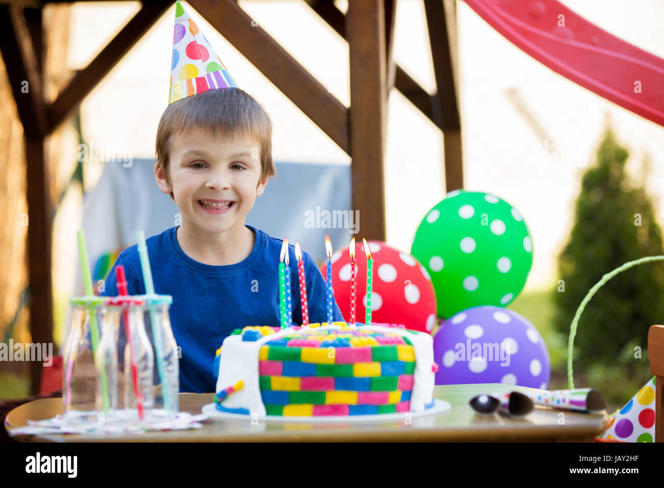 Sweet little child, boy, celebrating his sixth birthday, cake, balloons, candles, cookies. Childhood happiness concept - Stock Image