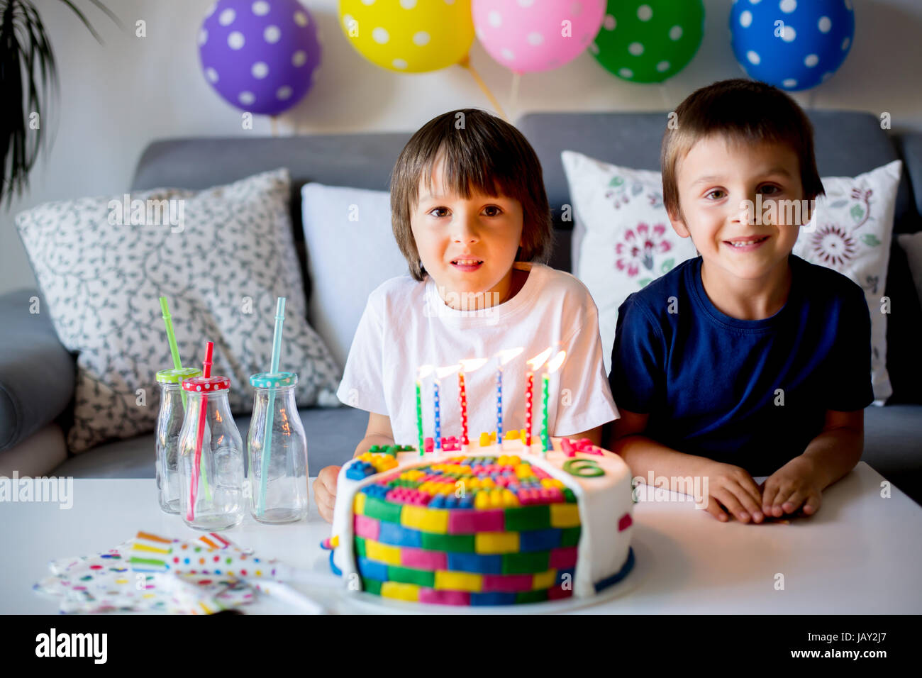 Sweet little child and his brother, celebrating his sixth birthday, cake, balloons, candles, cookies. Childhood - Stock Image