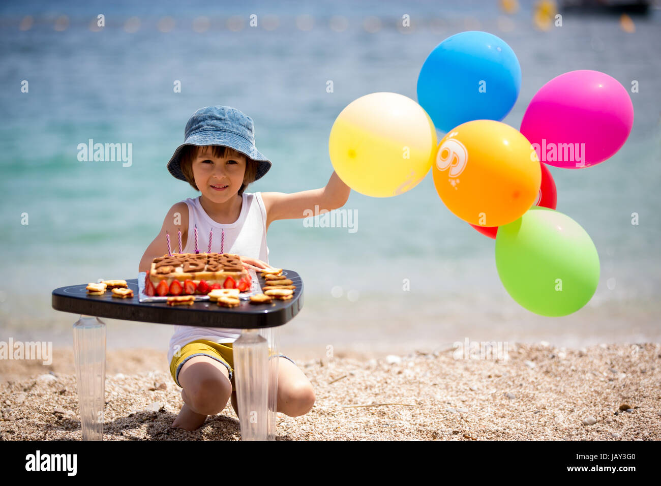 Sweet little child, boy, celebrating his sixth birthday on the beach, cake, balloons, candles, cookies. Childhood - Stock Image
