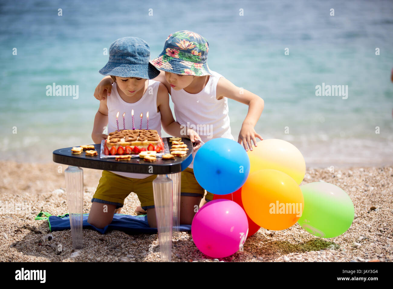 Sweet little children, twin boys, celebrating their sixth birthday on the beach, cake, balloons, candles, cookies. Stock Photo
