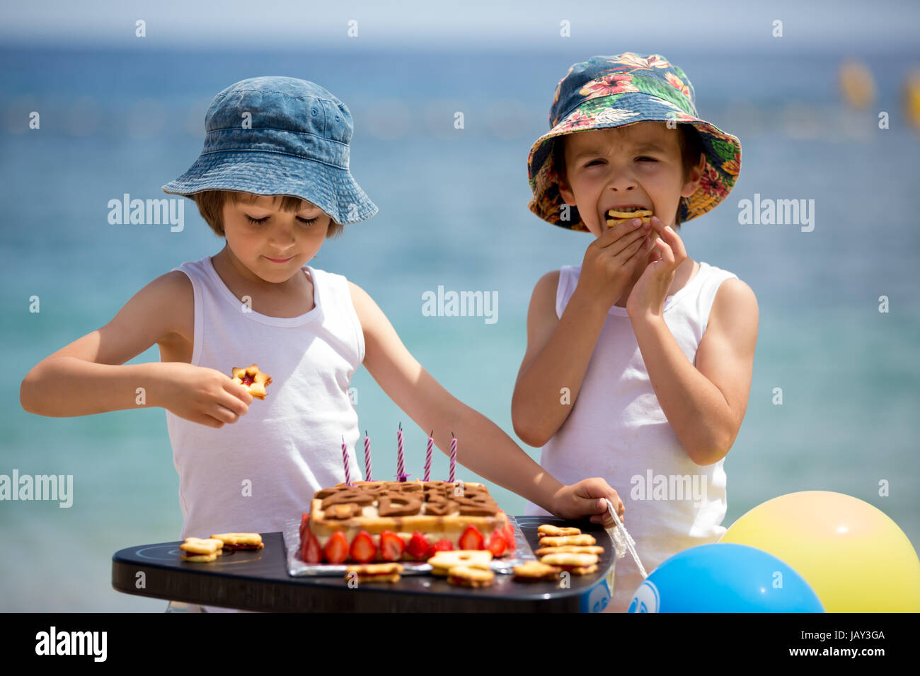 Sweet little children, twin boys, celebrating their sixth birthday on the beach, cake, balloons, candles, cookies. - Stock Image