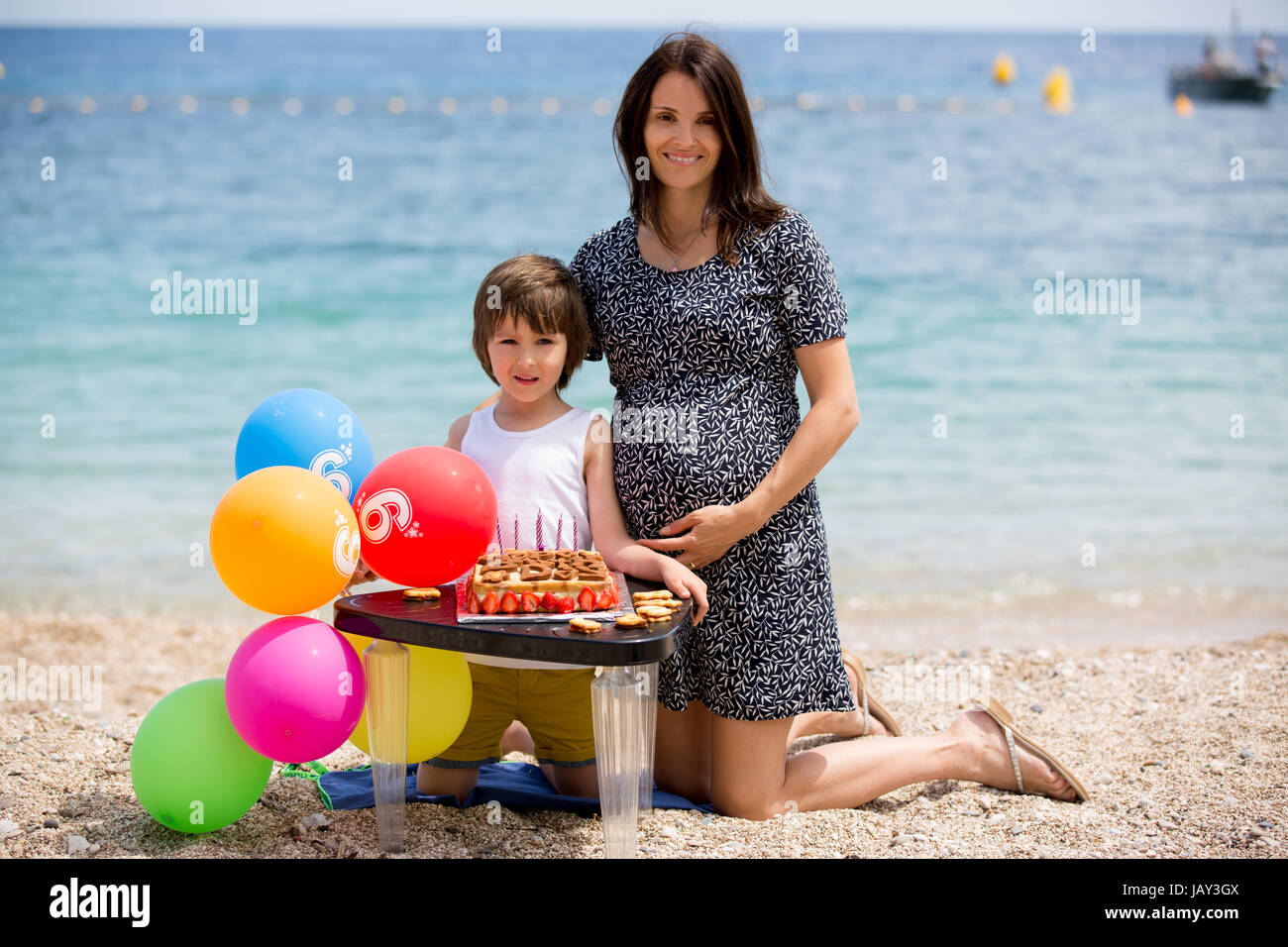 Sweet little child and his pregnant mom, celebrating his sixth birthday on the beach, cake, balloons, candles, cookies. Stock Photo