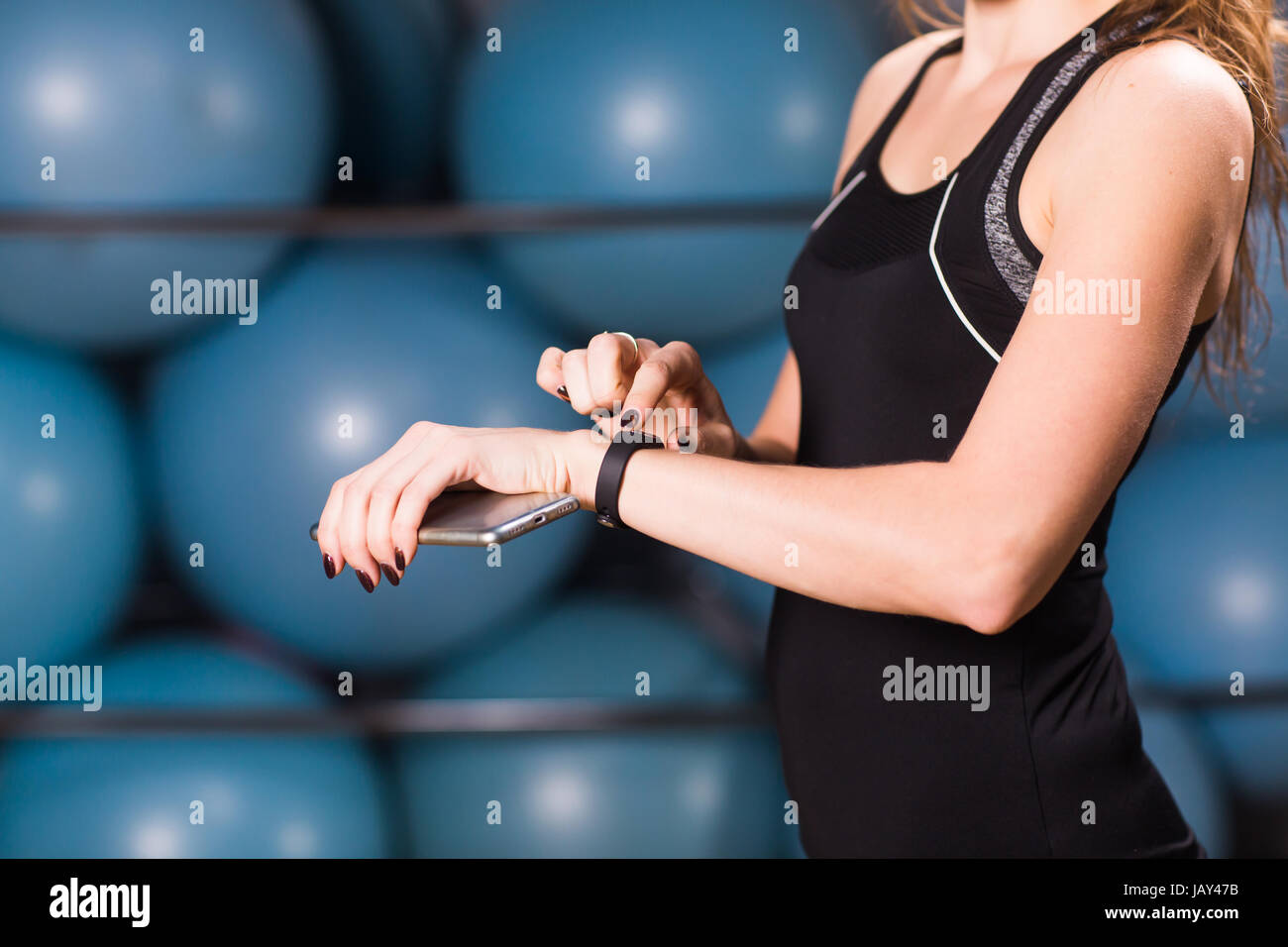 Close-up of female hands with fitness tracker and smartphone in gym - Stock Image