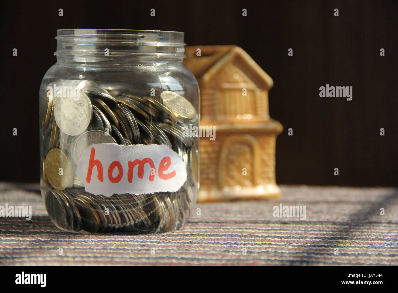 Coins in money jar with home label, finance concept - Stock Image