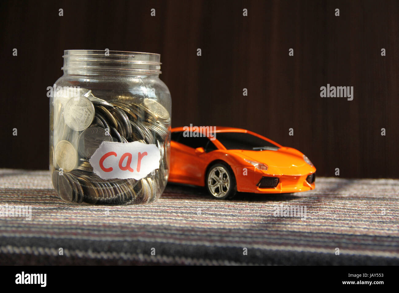 Coins in money jar with car label, finance concept Stock Photo
