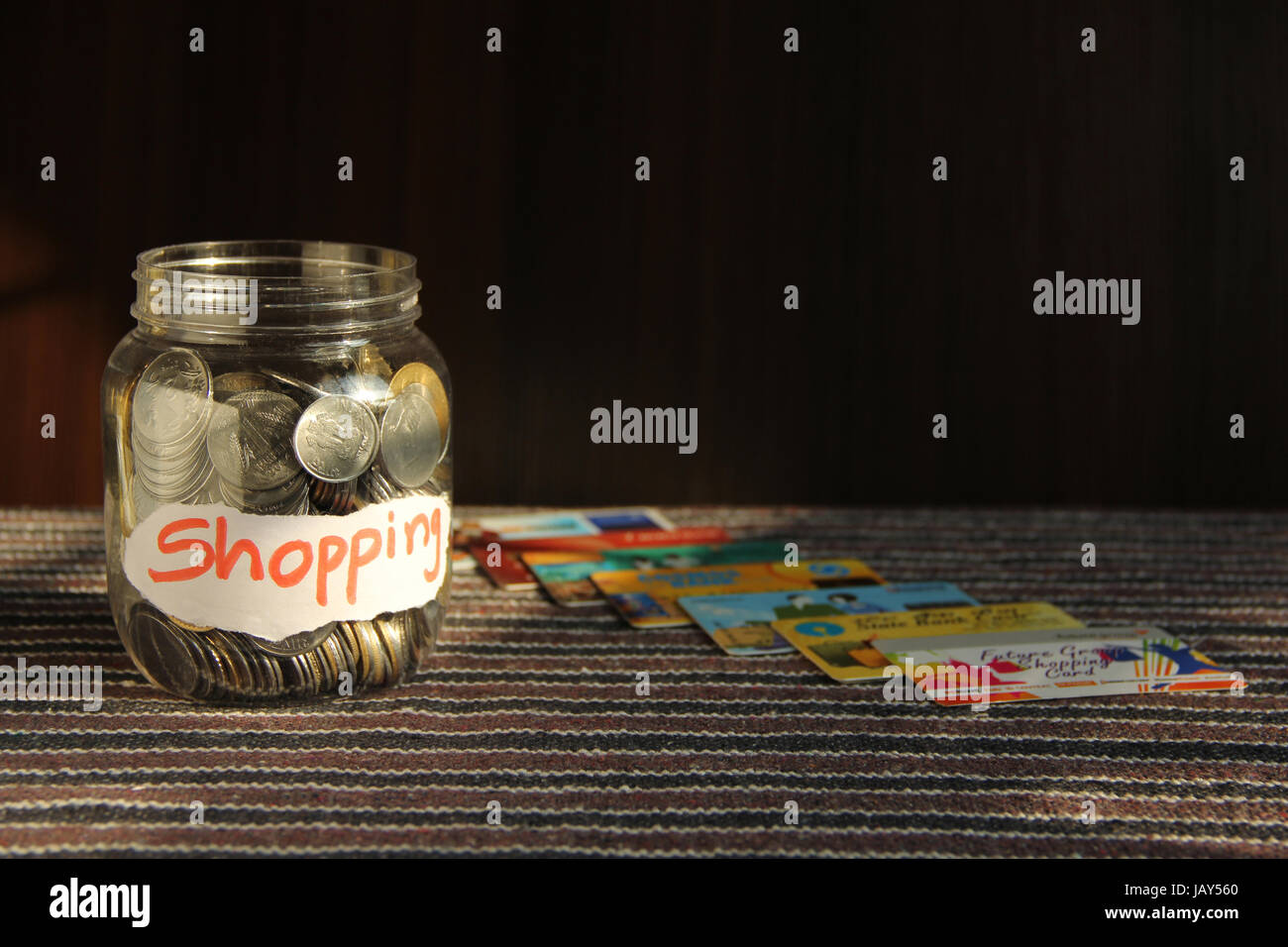 Coins in money jar with shopping label and credit cards, finance concept - Stock Image