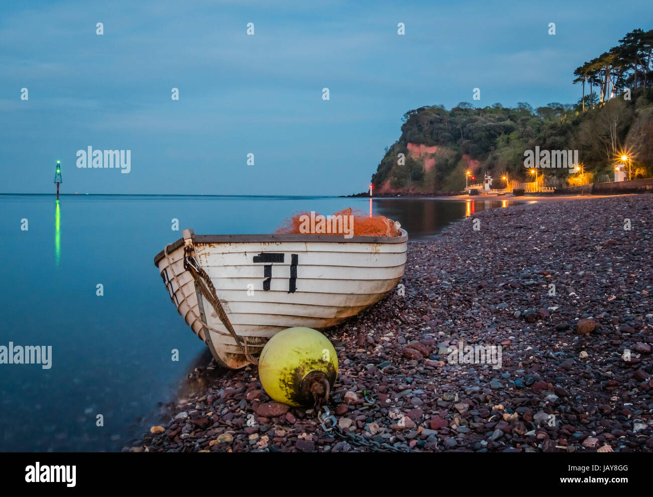 Boats on the red sanded beach at Shaldon in Devon at night. Stock Photo