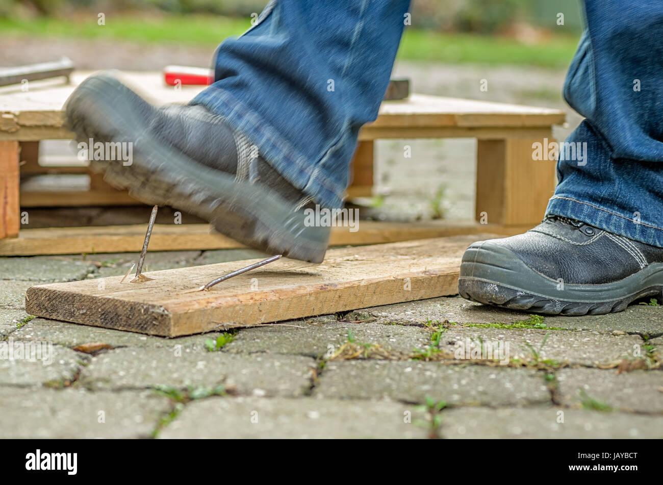 Arbeiter mit Sicherheitsschuhen tritt in einen Nagel Stock Photo
