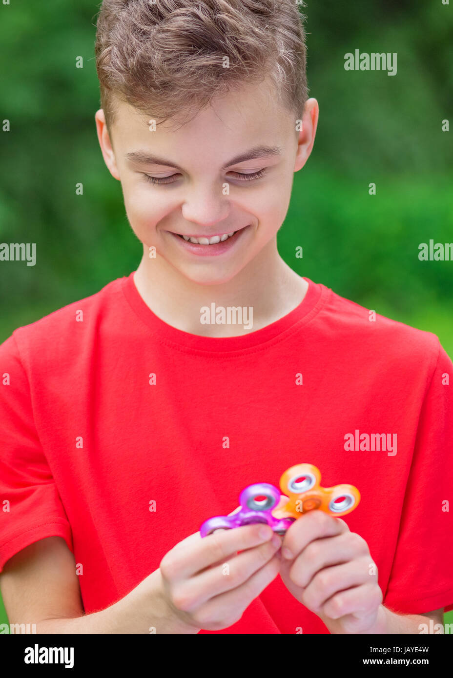 Young teen boy holding popular fidget spinner toy - outdoors portrait. Happy smiling child playing with a orange - Stock Image